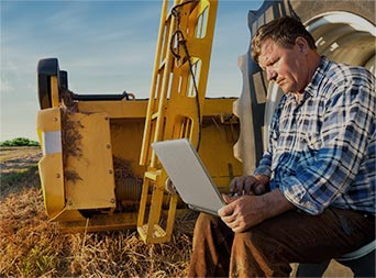 farmer sitting on a large tire checking energy use