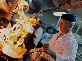 chef cooking over a stove in a restaurant kitchen