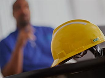 yellow hard hat with employee in background